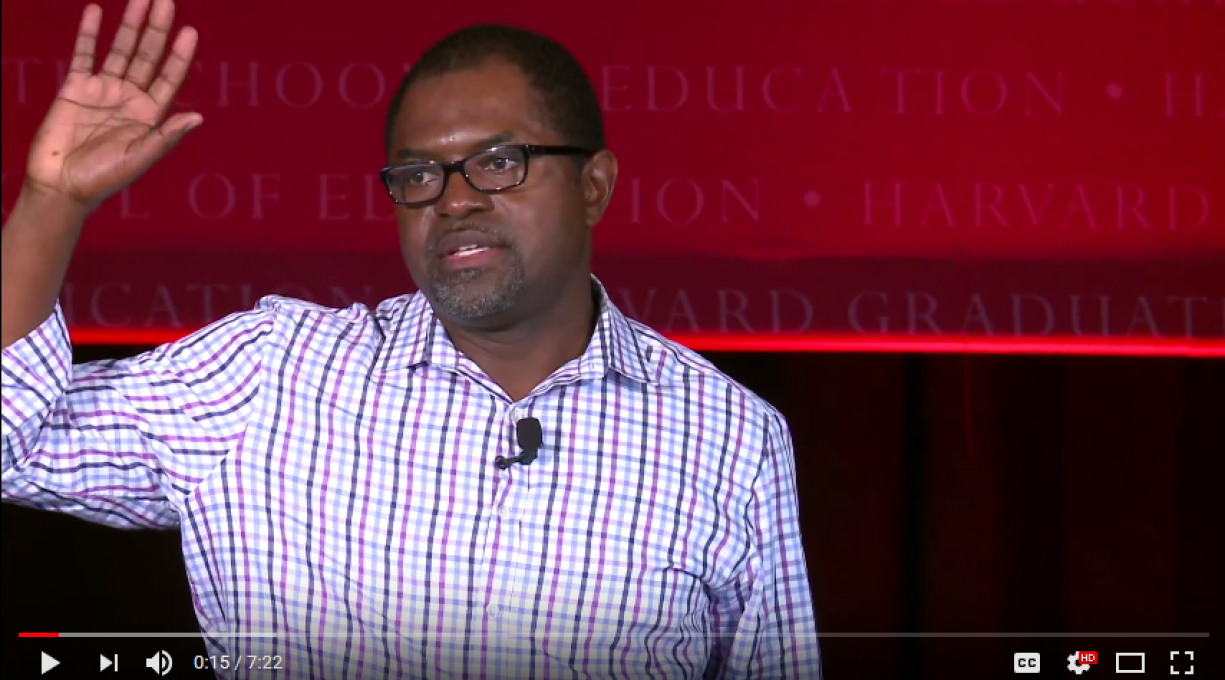 A screenshot of Irvin Scott on stage speaking