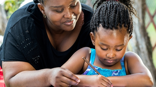 African American mother and her young daughter doing homework