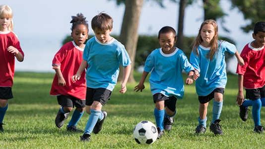 young kids on a field running after soccer ball