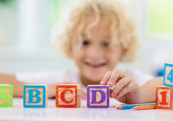 Child playing with wood letter blocks