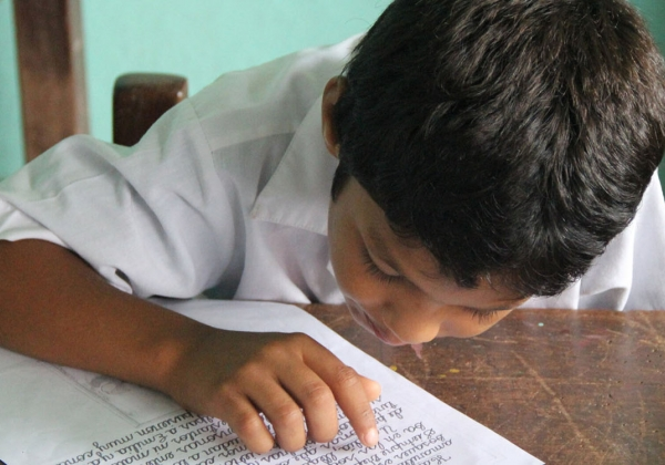 Peruvian boy at desk reading