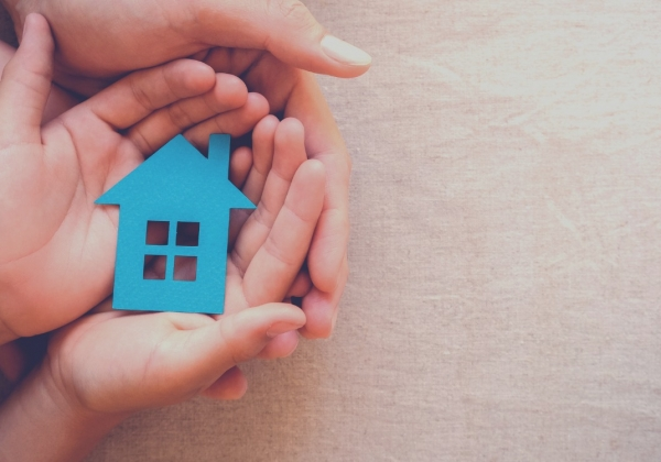 small blue schoolhouse in child's hand, cupped by adult hand