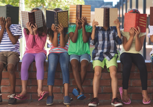 Diverse group of kids hiding behind books