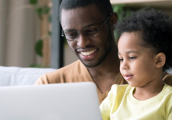 Parent looking at laptop with child