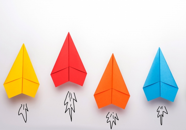 colorful paper airplanes flying upward