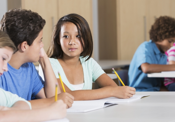 Photo of a female middle schooler looking seriously at a male classmate