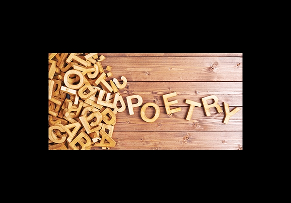 """jumble of wooden letter coming together to spell """"poetry"""""""