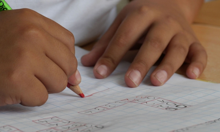 Child's hands doing math problem