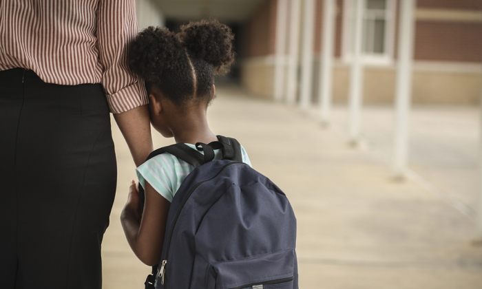 Child hugging parent's arm headed into school
