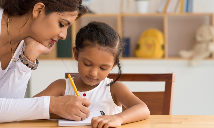 A mother helping her daughter with homework