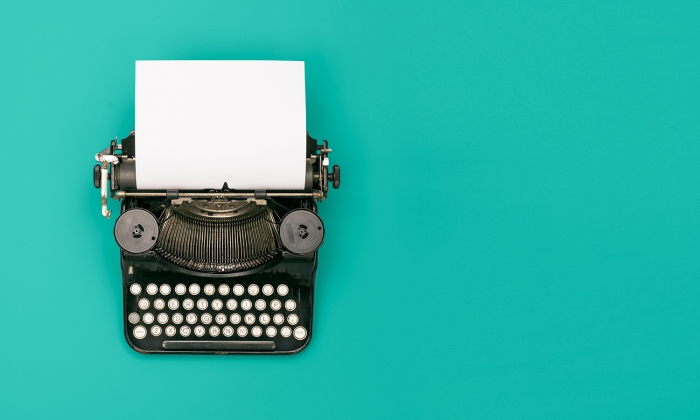 Photograph of a vintage typewriter against a turquoise background