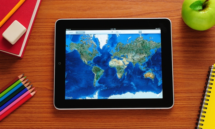 photo of google earth on an ipad, surrounded by school supplies