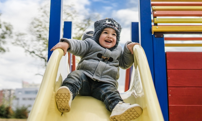 Happy child on playground slide