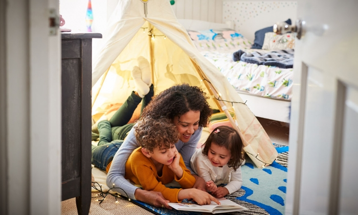 Mother reading to son and daughter in play tent