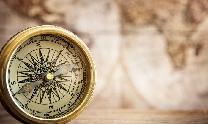 antique bronze compass, with blurry antique map in the background