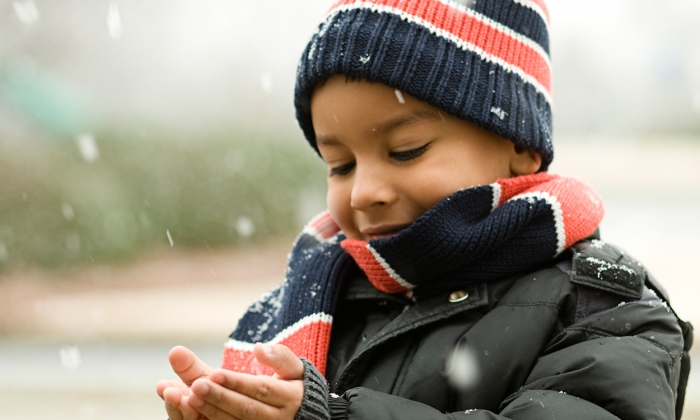 boy in winter coat, hat, scarf catching snowflakes