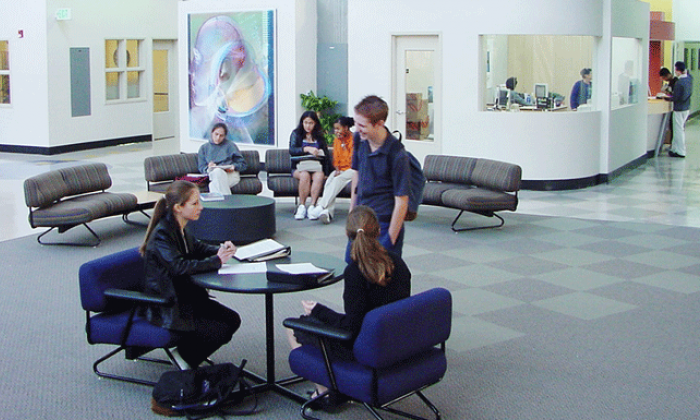 photo of a new school building, with students in open lobby area