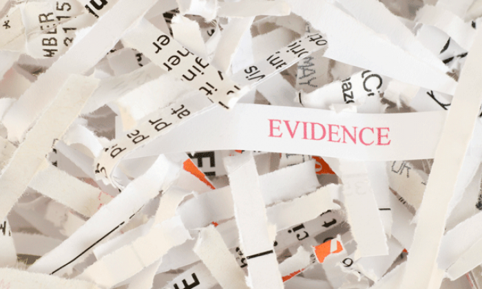 shredded paper with one piece that says evidence