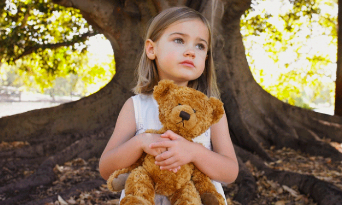 A small girl holds onto a teddy bear