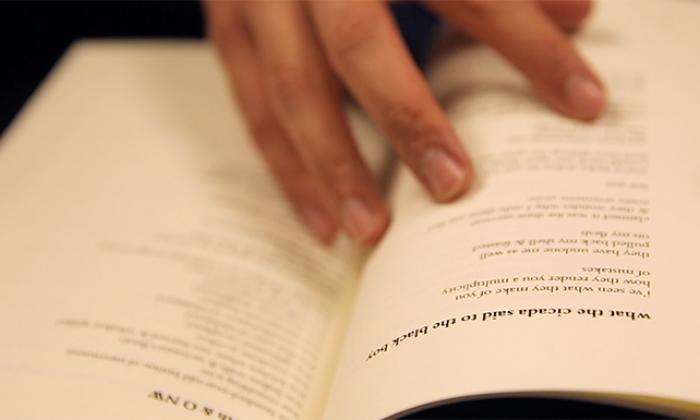 Hands shown opening a book of poems