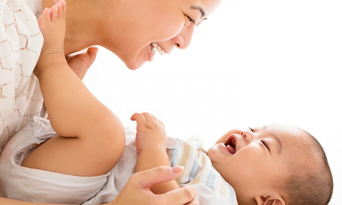 A laughing mother looking down at her smiling baby