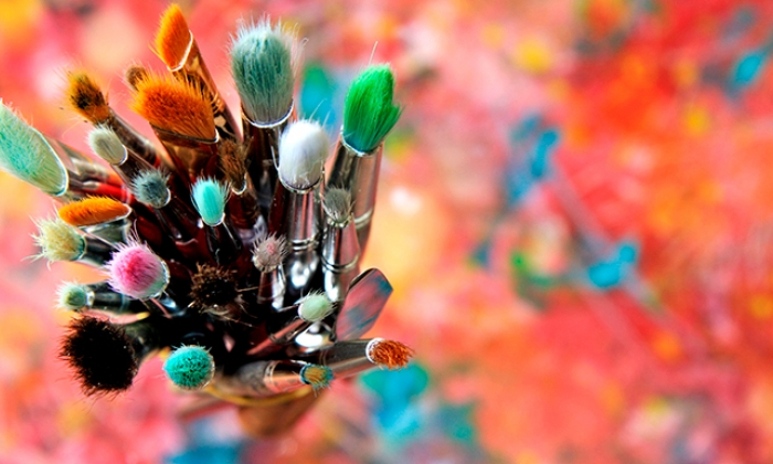 paint brushes against colorful background