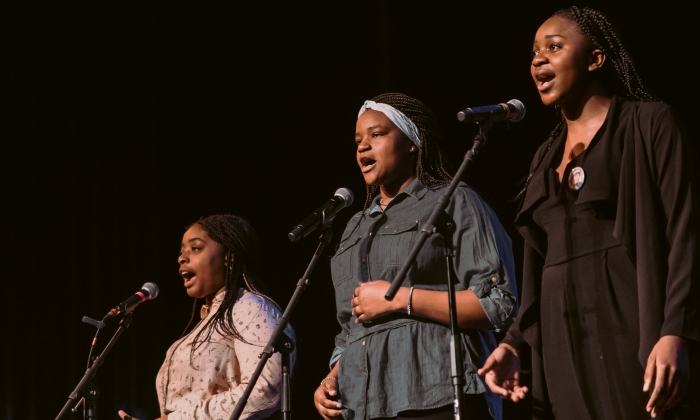 Photo of three African American female students standing at microphones