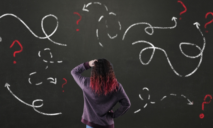 Photo of a teenaged girl looking confused in front of a blackboard with many arrows