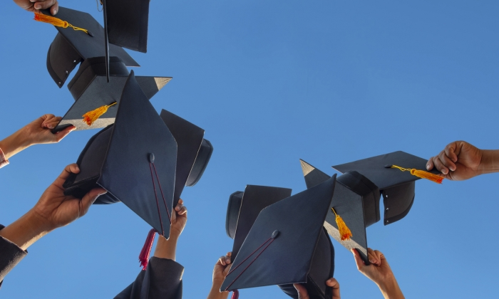 Graduation caps held in the air