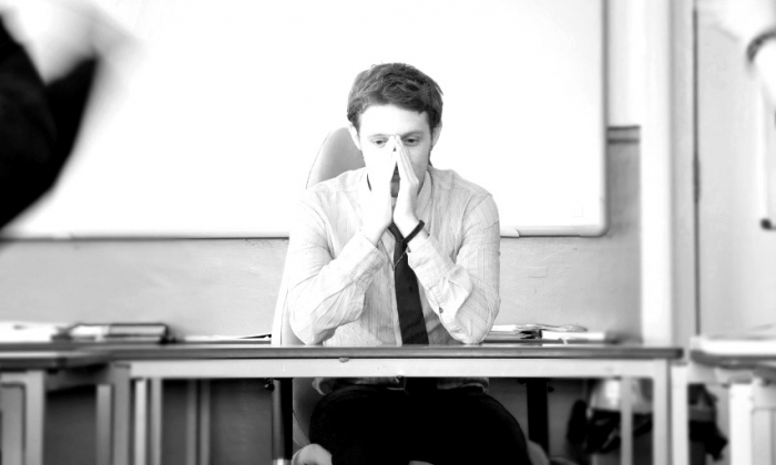 Teacher at desk with head in hands