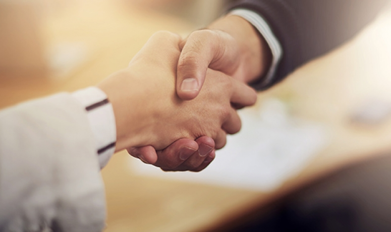 two adults shaking hands