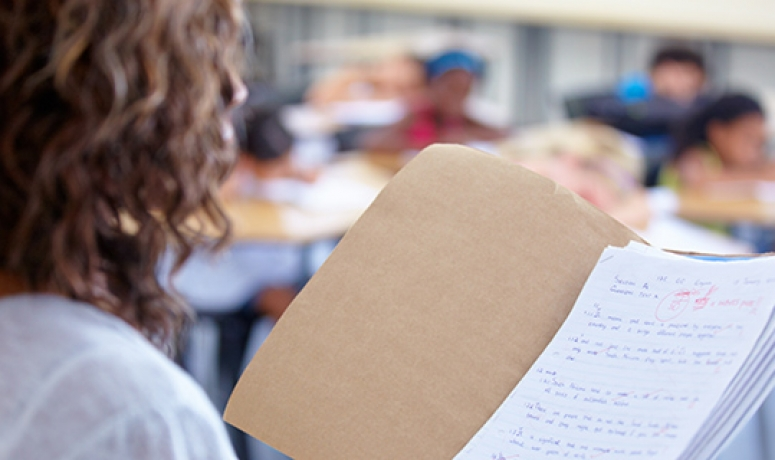 conceptual photo of teacher holding folder of graded papers
