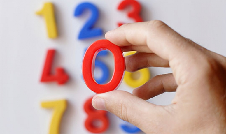a child's number magnets, with hand holding a zero