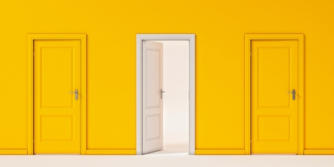 two closed yellow doors against a yellow background, with one white door that's open to light