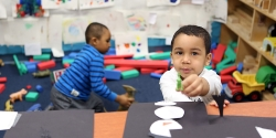 Preschool boy with art project, with another boy playing in the background