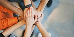A circle of hands placed on top of one another, suggesting unity