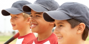 Three boys wearing baseball caps