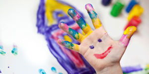 A child's hand covered in finger paint