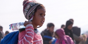 Refugee girl holds water bottle