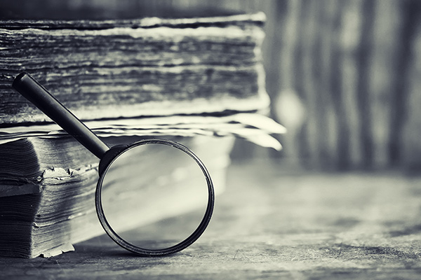 An image of books and a magnifying glass