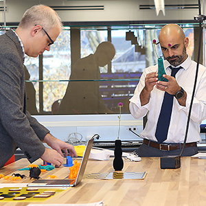 Two men work on projects in the Education Innovation Studio