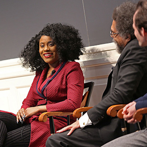 A woman smiling as she sits on a panel