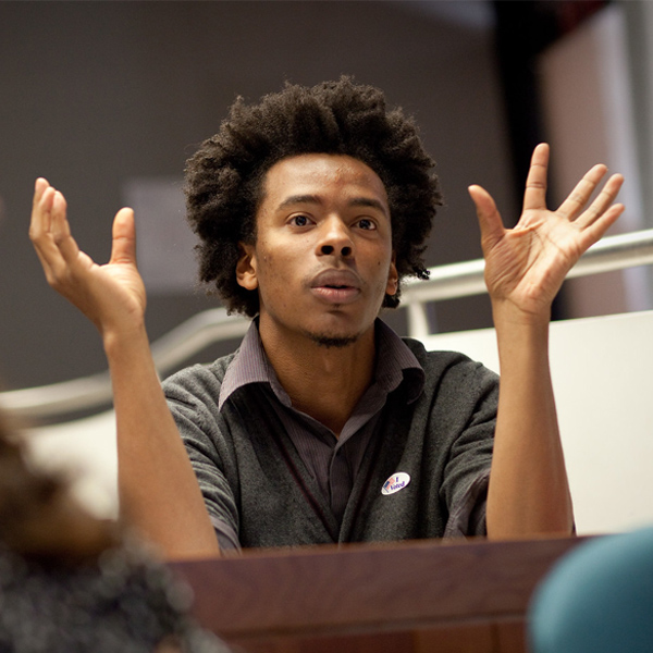 An HGSE student gestures as he speaks in class.