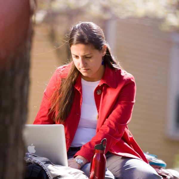An HGSE student works on a laptop outside.