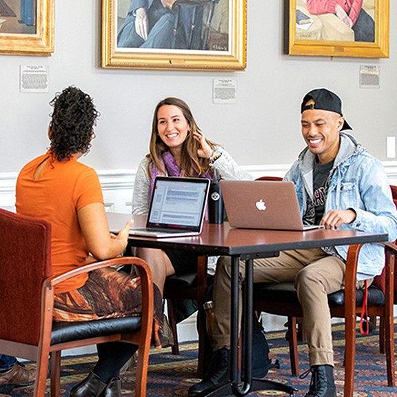 HGSE students work together at a table on campus.